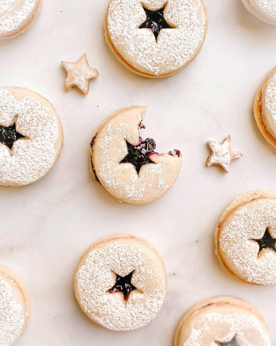 gluten-free linzer cookies with stars cut into the middle of the cookies, blueberry jam can be see through the star cutout