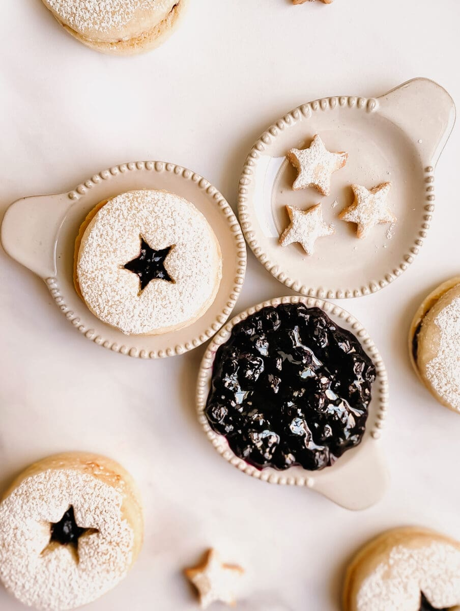 gluten-free linzer cookie, pastry stars, and blueberry jam in small ceramic plates