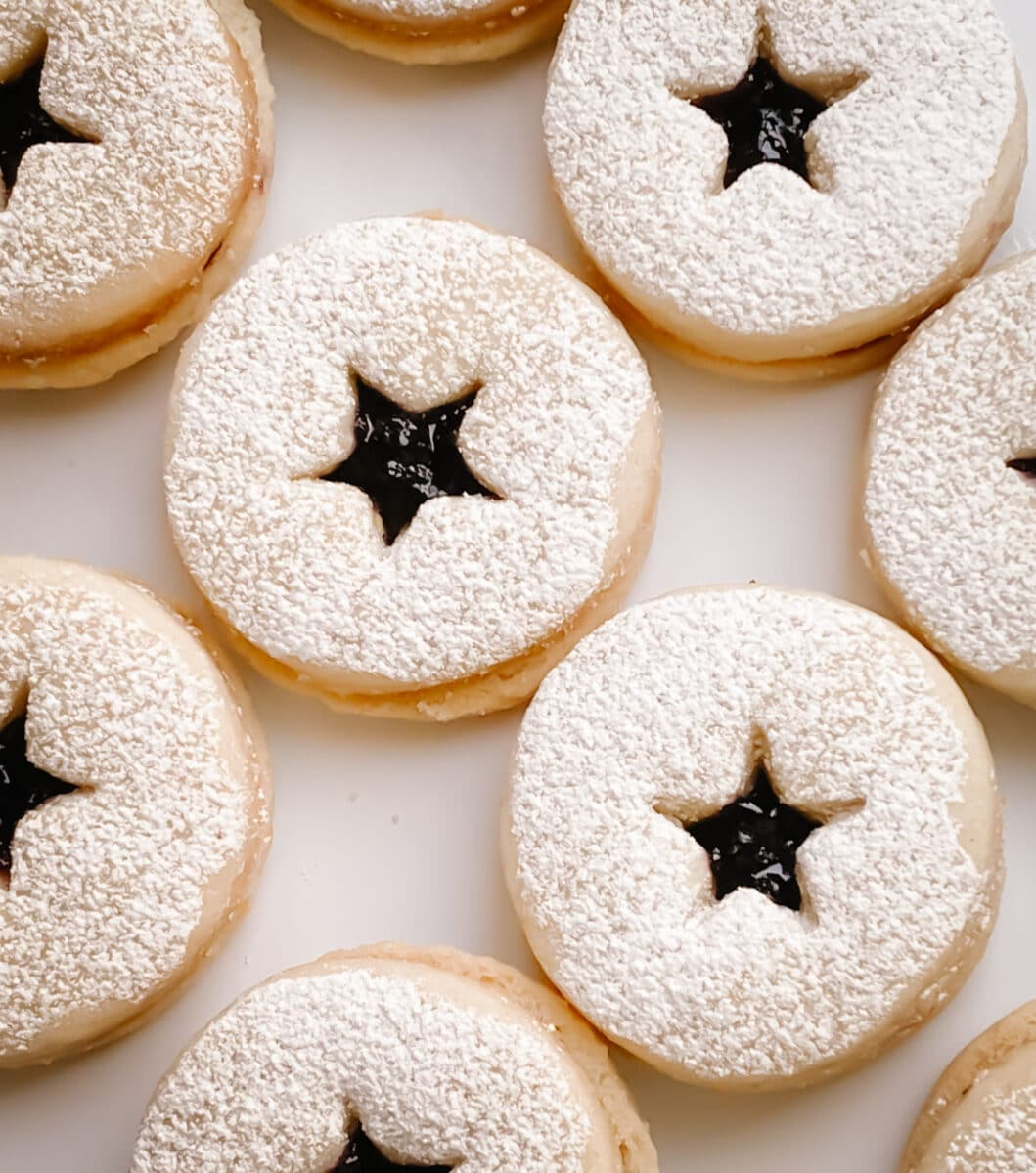 blueberry jam linzer cookies with a dusting of power sugar, a variety of cookies laid out