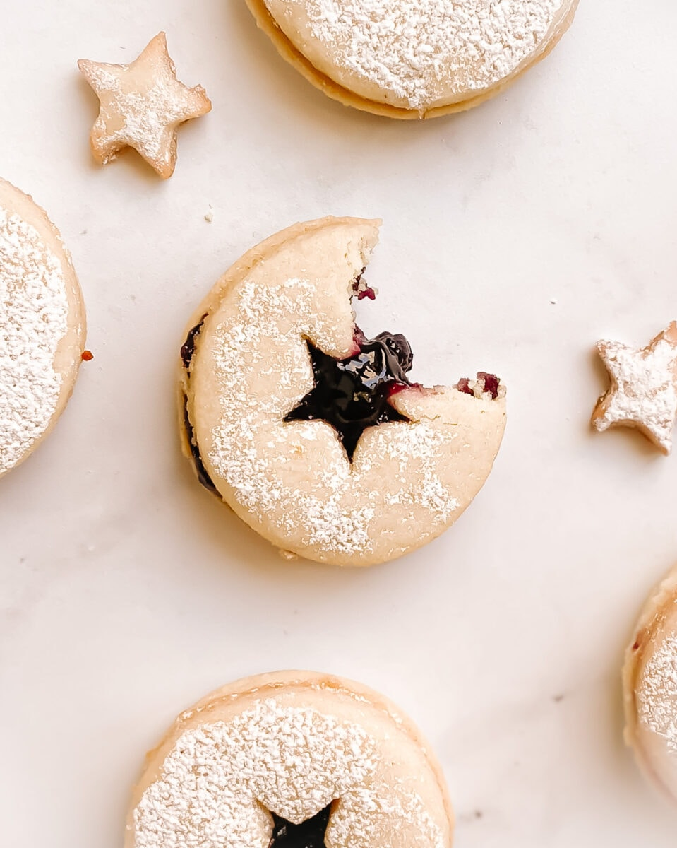 linzer cookie with a bite take out of it, blueberry jam leaking out of the cookie