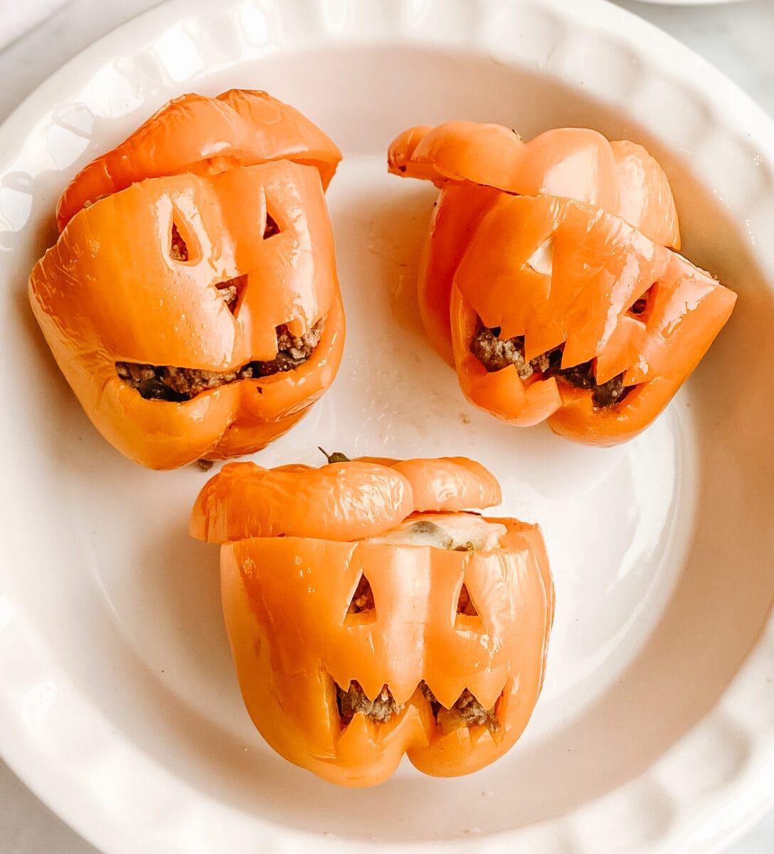 orange peppers with halloween faces on them looking up at the camera in a white ceramic bowl