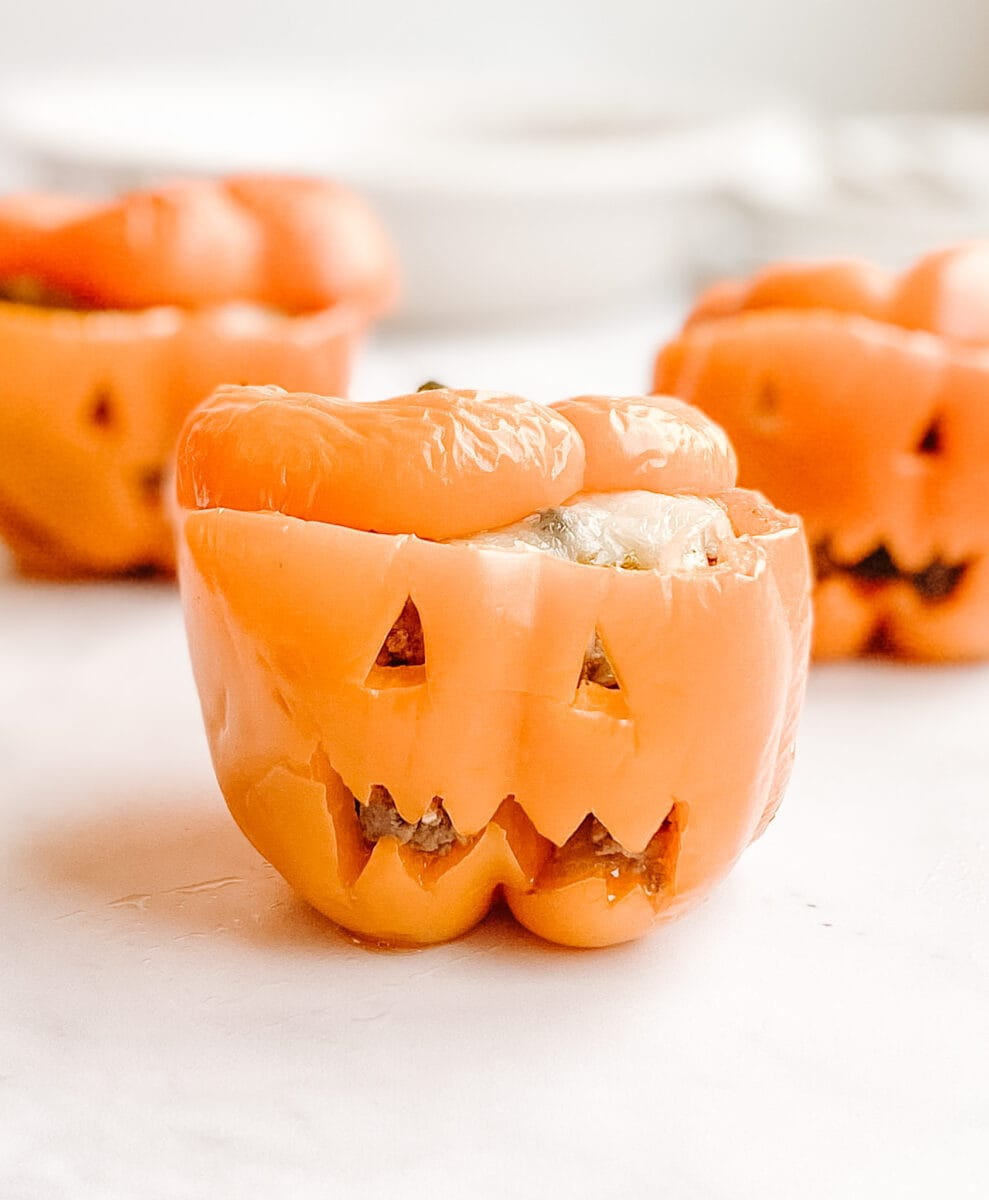 three gluten-free jack-o-lantern stuffed orange peppers, peppers have faces on them with triangle eyes and a mouth with teeth