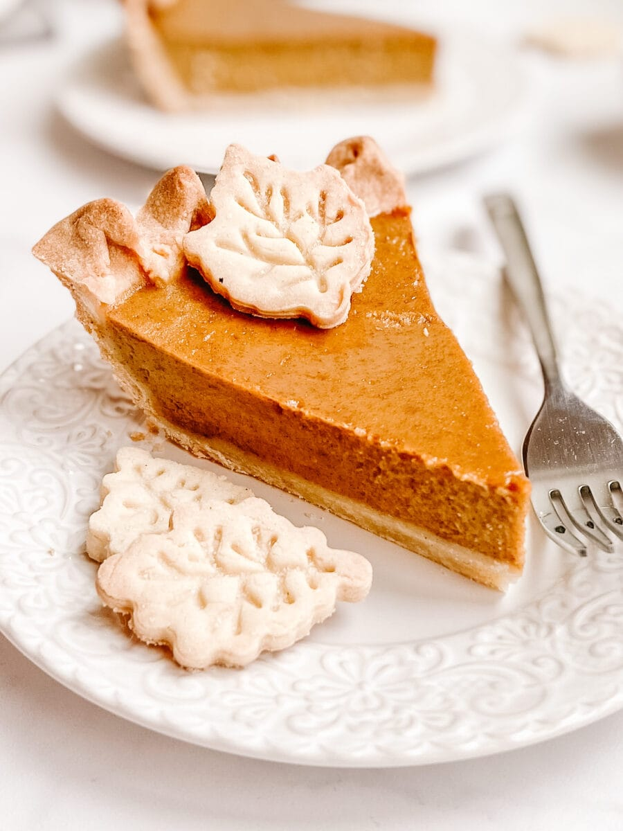 slice of pumpkin pie on lattice decorative white plate with silver fork and pastry leaves