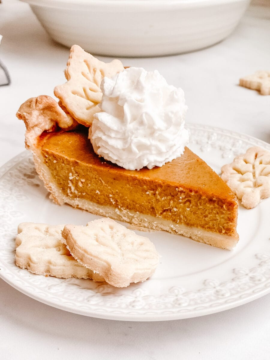 gluten free pumpkin pie with pastry leaves and whipped cream