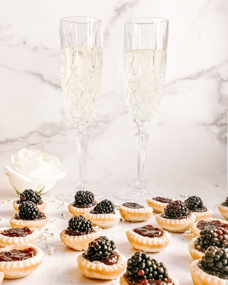 a spread of mini blackberry tarts, two champagne glasses with champagne in the background