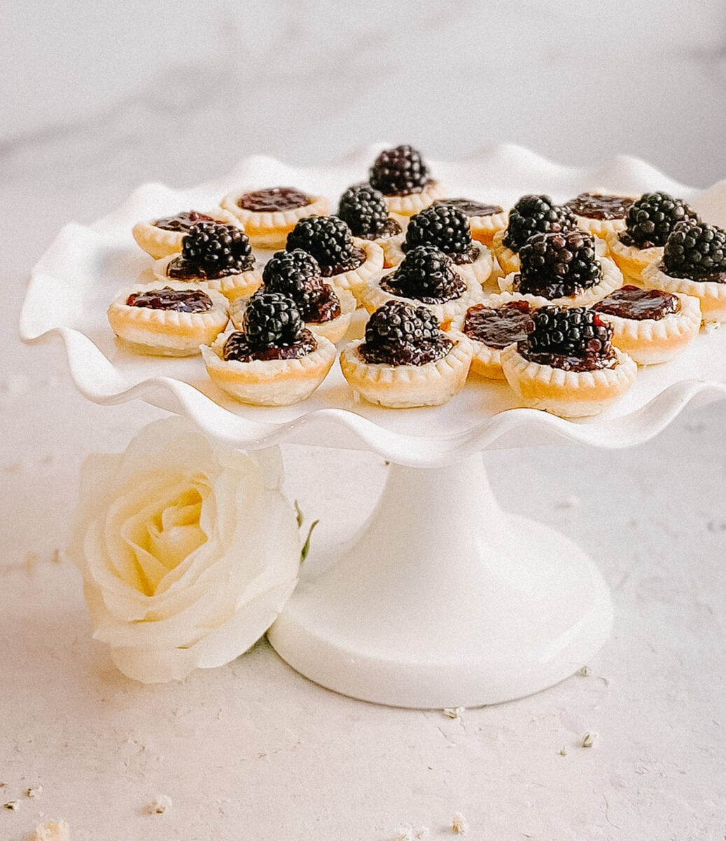 gluten-free blackberry tarts on a white cake stand, white flowers adjourn the base of the stand