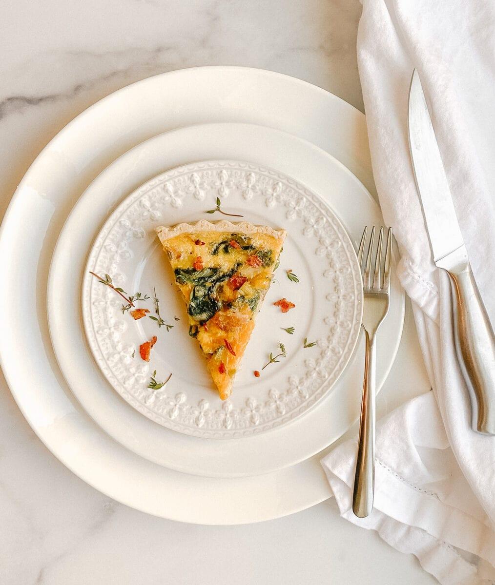 a slice of quiche on a decorative white plate