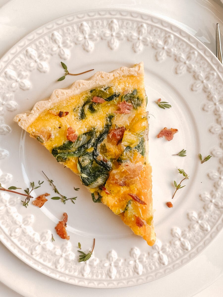 zoomed in shot of gluten-free quiche on a white decorative plate, spinach and bacon can be seen clearly