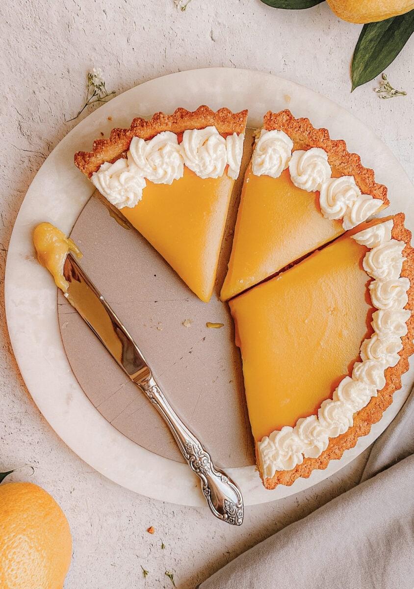 gluten free lemon tart on marble slab cut into slices half the tart missing knife with lemon filling near by