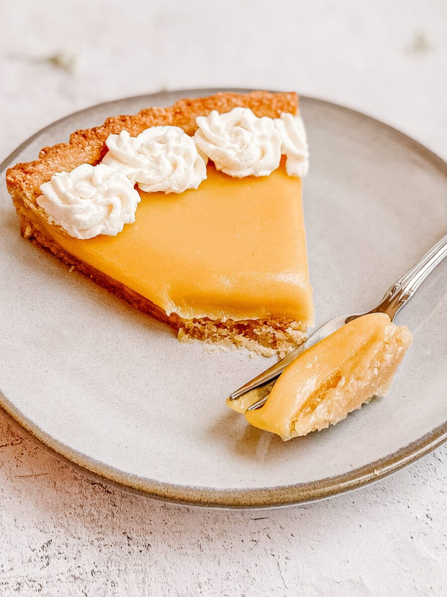 gluten free lemon tart slice view from the front, tip of the slice is on a fork