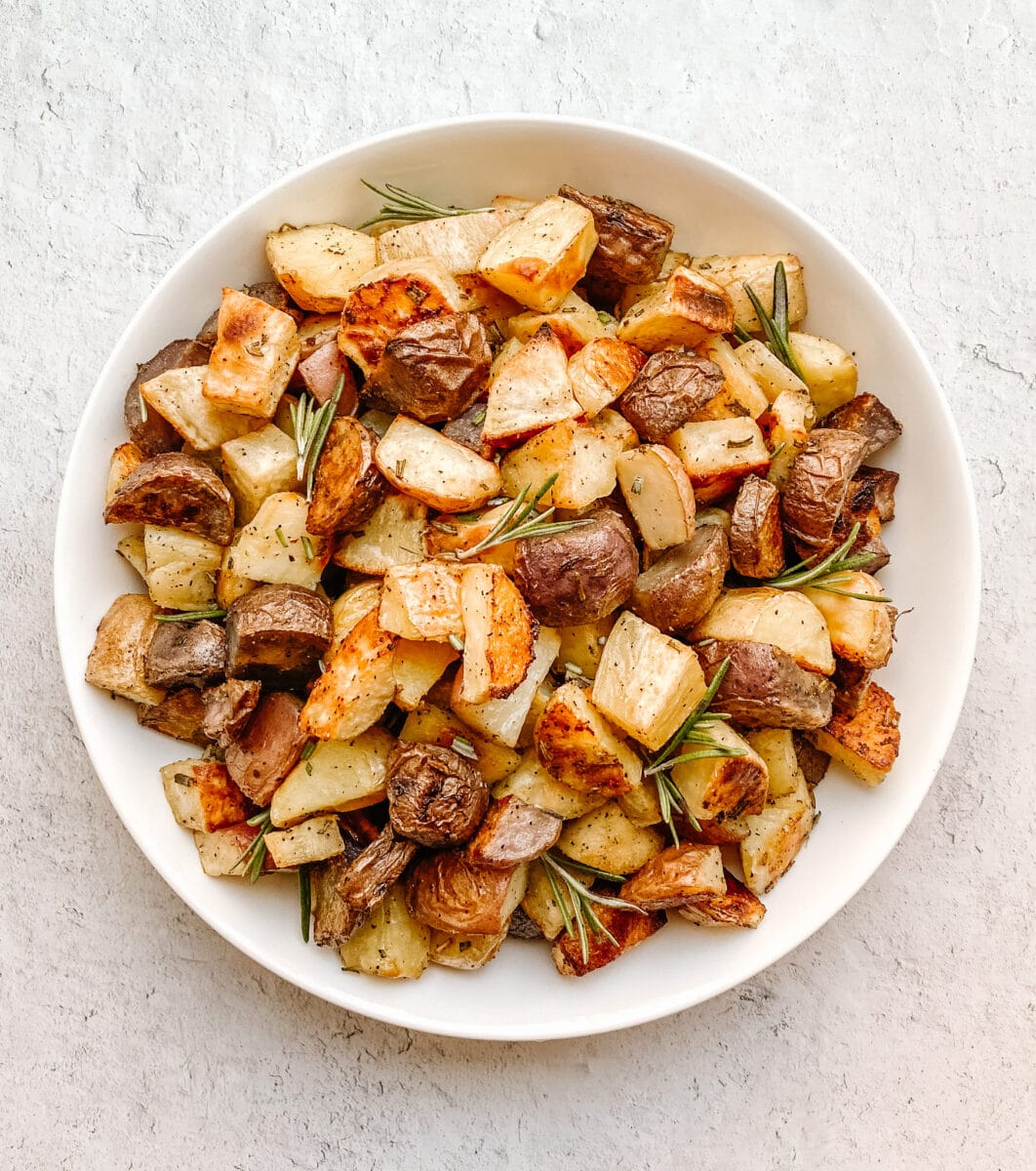 gluten free potatoes in a bowl taken from an aerial view with sprigs of rosemary throughout