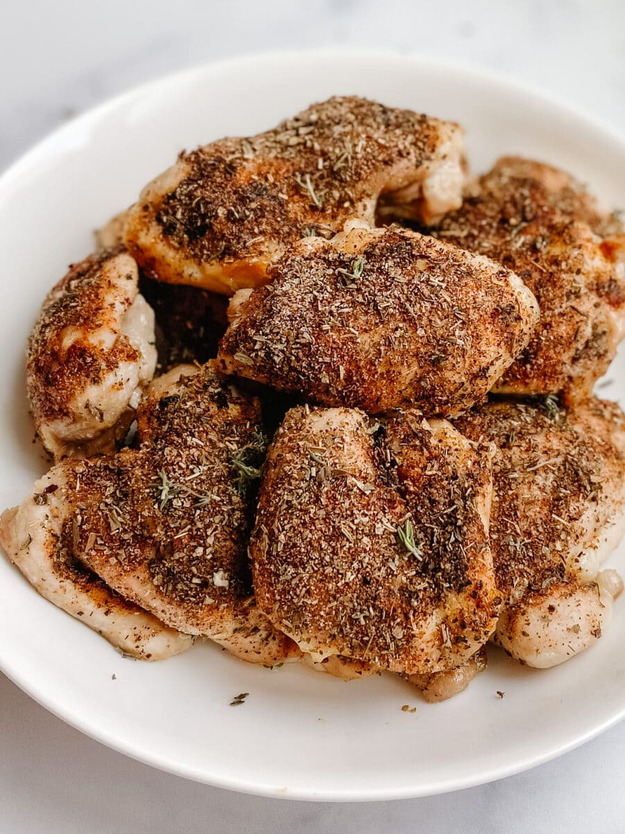 gluten free baked chicken piled onto a white plate with seasonings on top