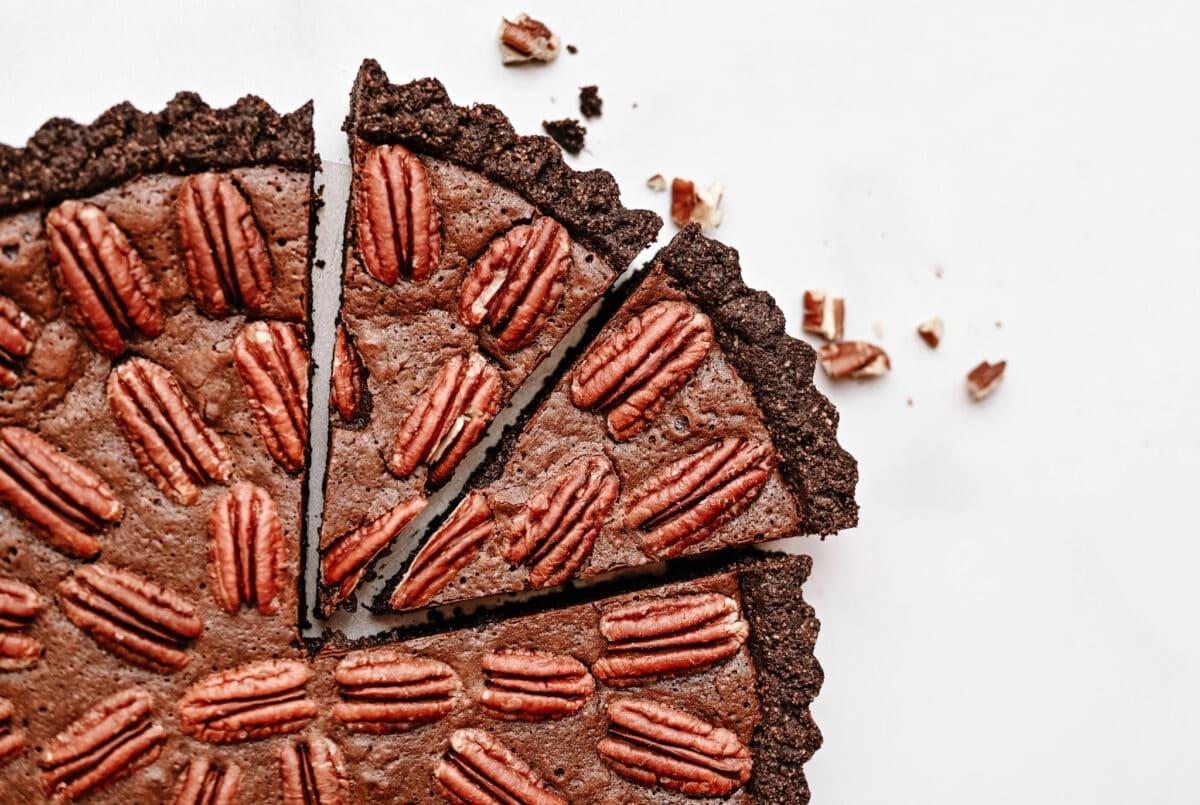 gluten-free chocolate pecan tart close up shot, tart has a chocolate crust