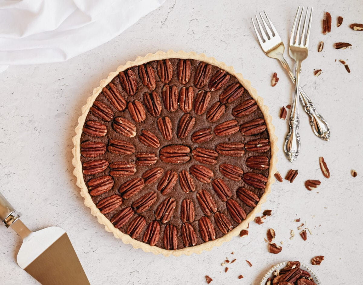 whole chocolate pecan tart shot from an aerial view, chopped pecans can be seen around the tart and white silverware