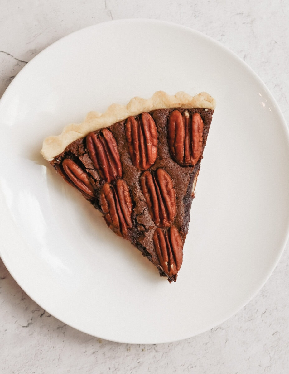 slice of gluten-free chocolate pecan tart on a while plate