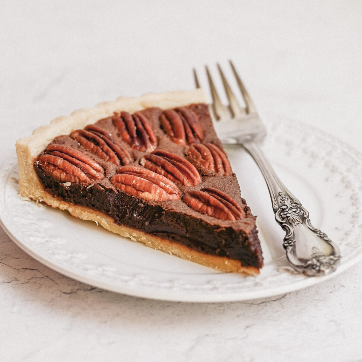 close up shot of a slice of chocolate pecan tart, on a white decorative plate with a silver fork