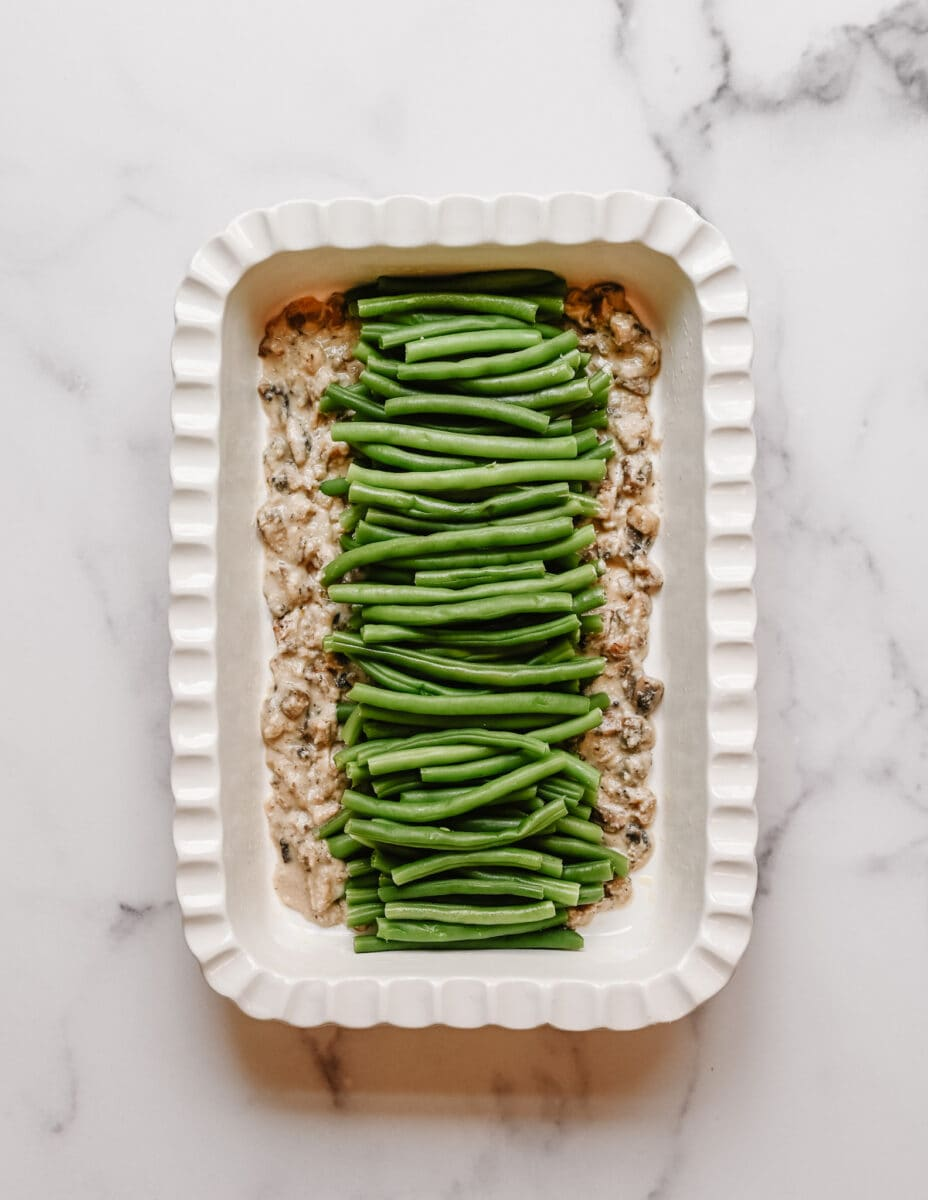 green bean casserole evenly displayed in a white fluted ceramic baking dish.