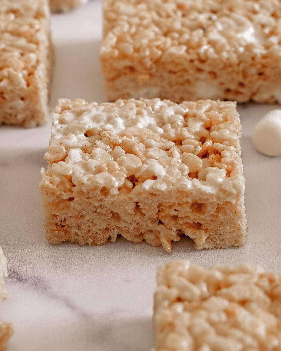 Top view of several rice krispie treats focussed on one center rice krispies treat in the middle on a marble board.