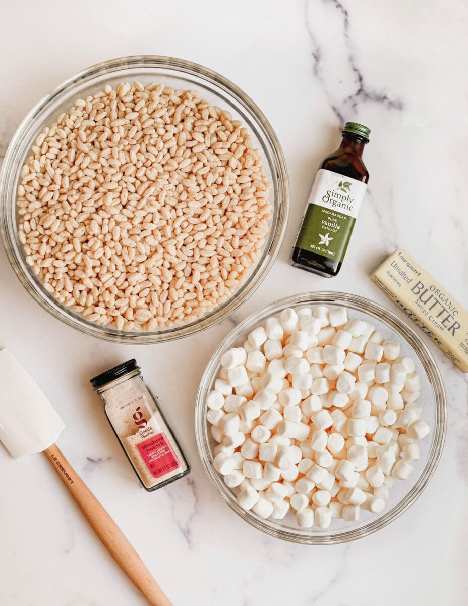 rice krispies cereal in a glass bowl, marshmallows in a glass bowl, a bottle of vanilla extract, a bottle of salt, a stick of butter, and a white rubber spatula with wooden handle.