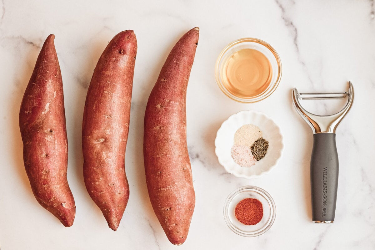 image of ingredients for roasted sweet potatoes; sweet potatoes, salt, pepper, garlic, and oil.