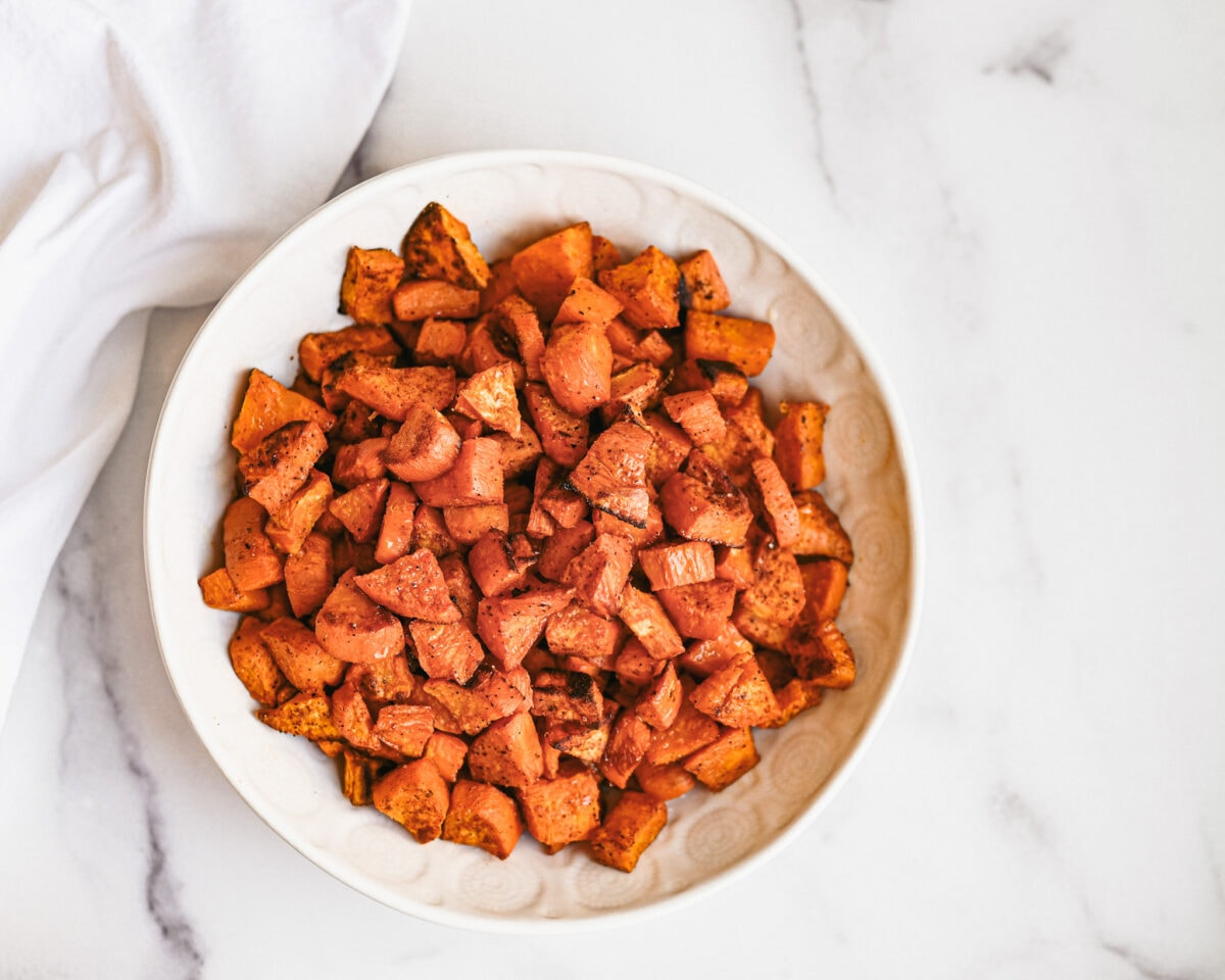 zoomed out look at roasted sweet potatoes in white bowl on granite top