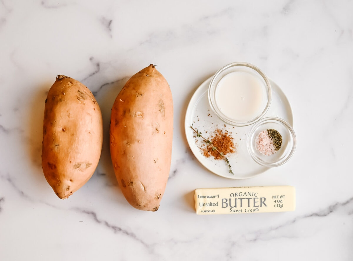 2 white sweet potatoes, milk in a bowl, pinch of salt and pepper in a bowl, nutmeg and stick of butter